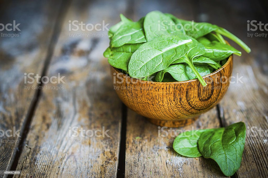 Fresh spinach in a wooden bowl on a wooden table background stock photo