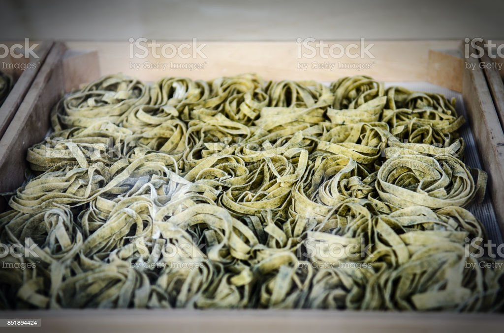 fresh spinach noodles in a wooden box stock photo