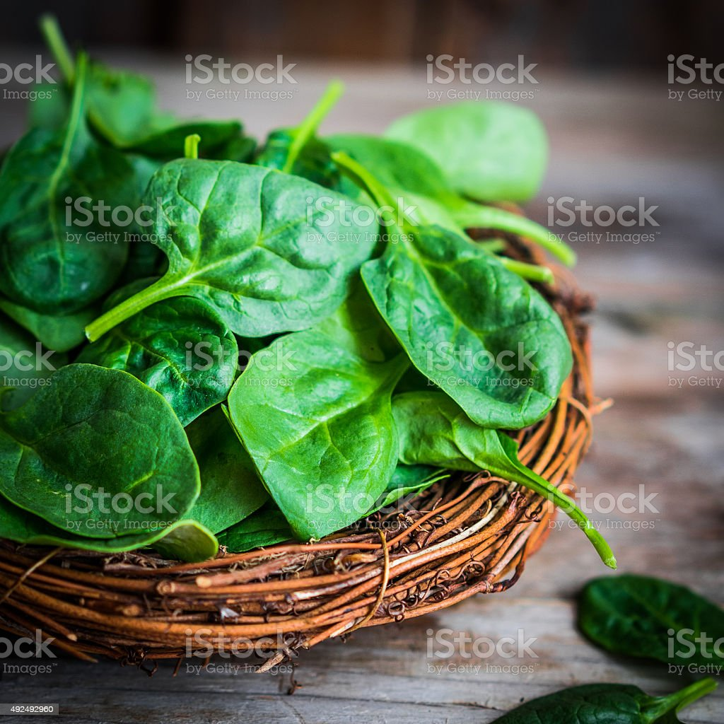 Fresh spinach on rustic wooden background stock photo