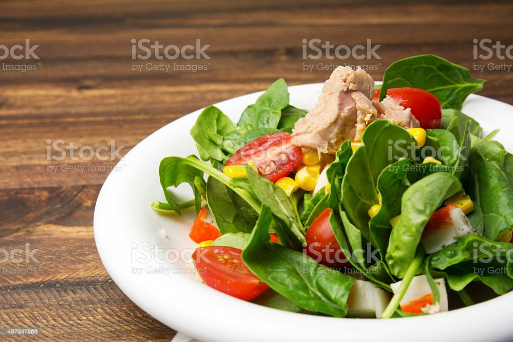 Fresh spinach salad with tuna and corn, cherry tomatoes stock photo
