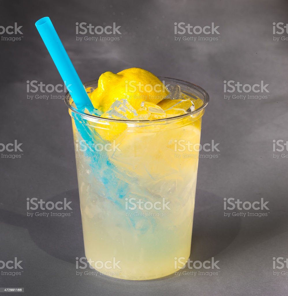 Fresh squeezed lemonade in a clear cup and blue straw. stock photo