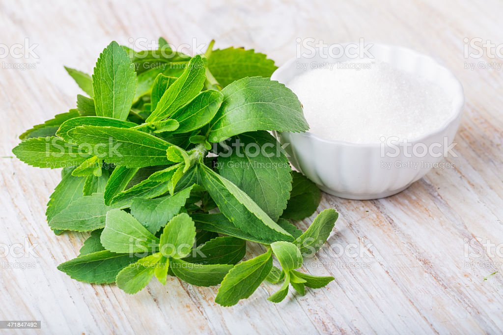 Fresh stevia leaves and bowl with sugar stock photo