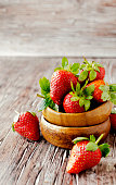 Fresh strawberries in a wooden bowl, selective focus