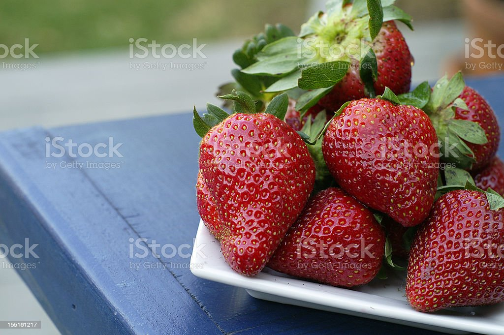 Fresh Strawberries on Table in Outdoor Setting royalty-free stock photo