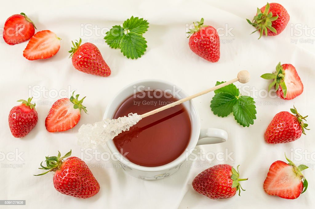 Fresh strawberries with strawberry juice on white fabric stock photo