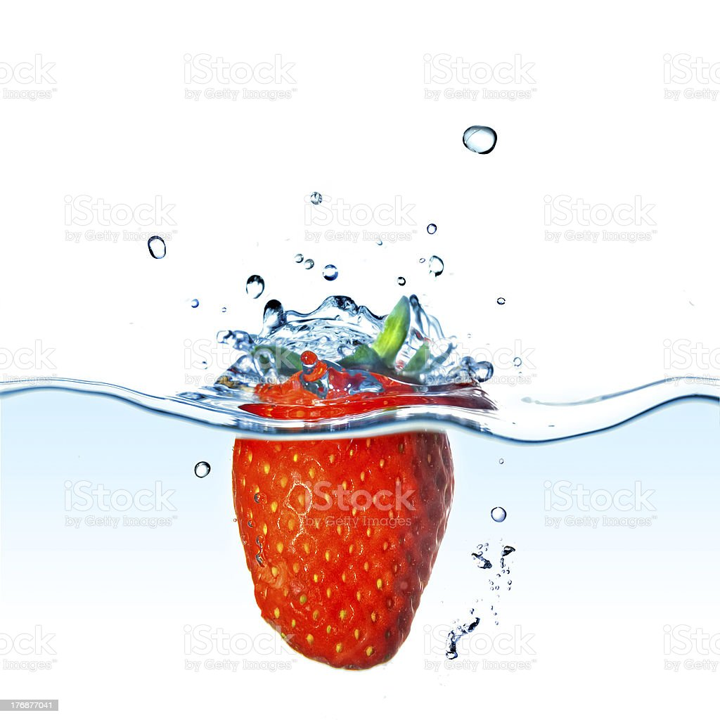 Fresh strawberry dropped into water with bubbles isolated on white royalty-free stock photo