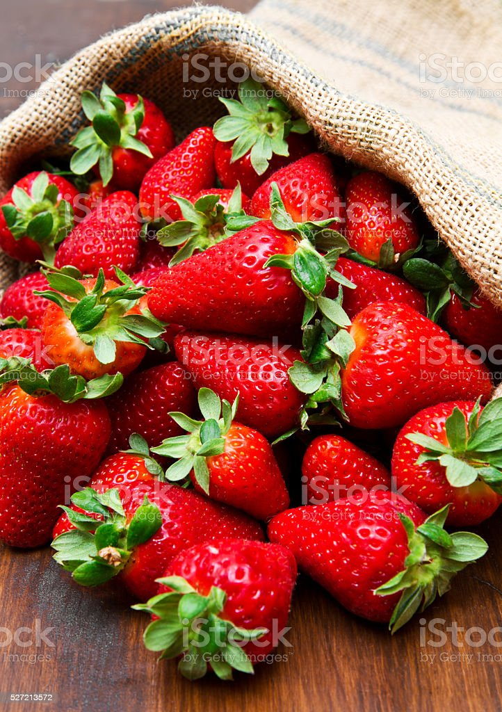 fresh strawberry in burlap sack on wood stock photo