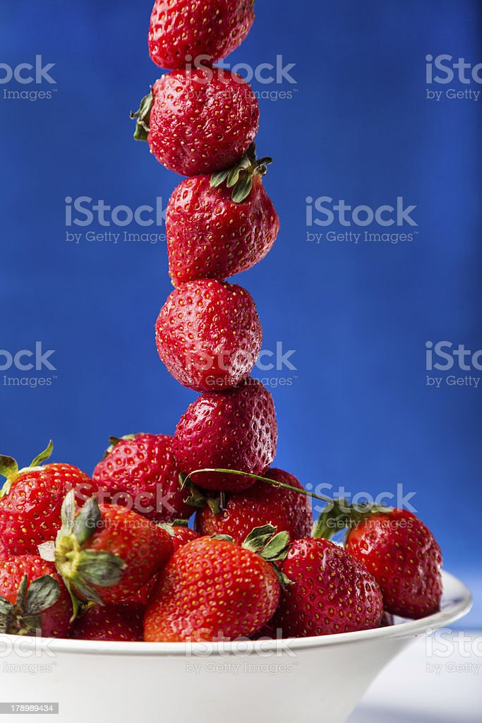 fresh strawberry in white plate on blue background royalty-free stock photo