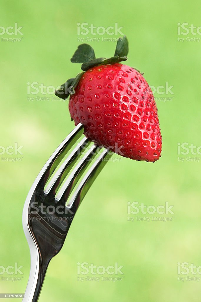 Fresh strawberry on the fork against a green background royalty-free stock photo