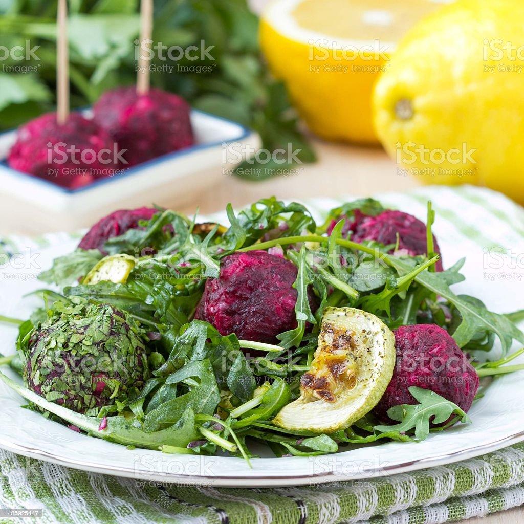 Fresh summer salad with arugula, zucchini, balls of beet stock photo