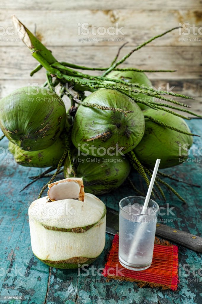 Fresh super healthy coconut water in a drinking glass with a paper drinking straw. stock photo