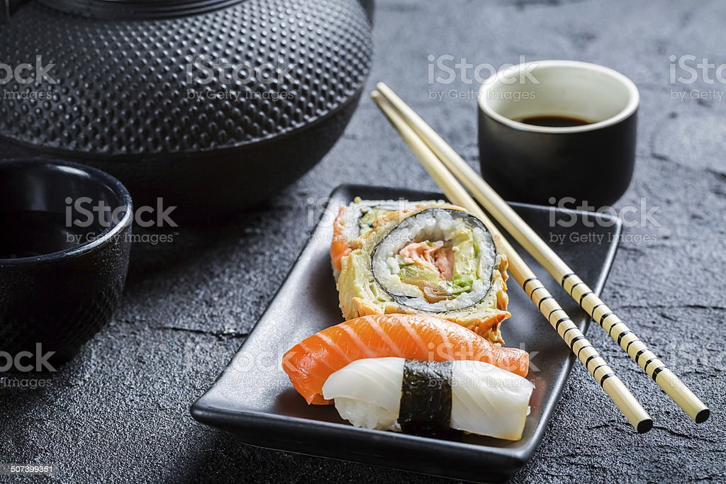Fresh sushi served in a black ceramic stock photo