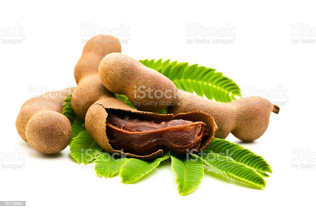 Fresh tamarind one open on green leaves white back stock photo