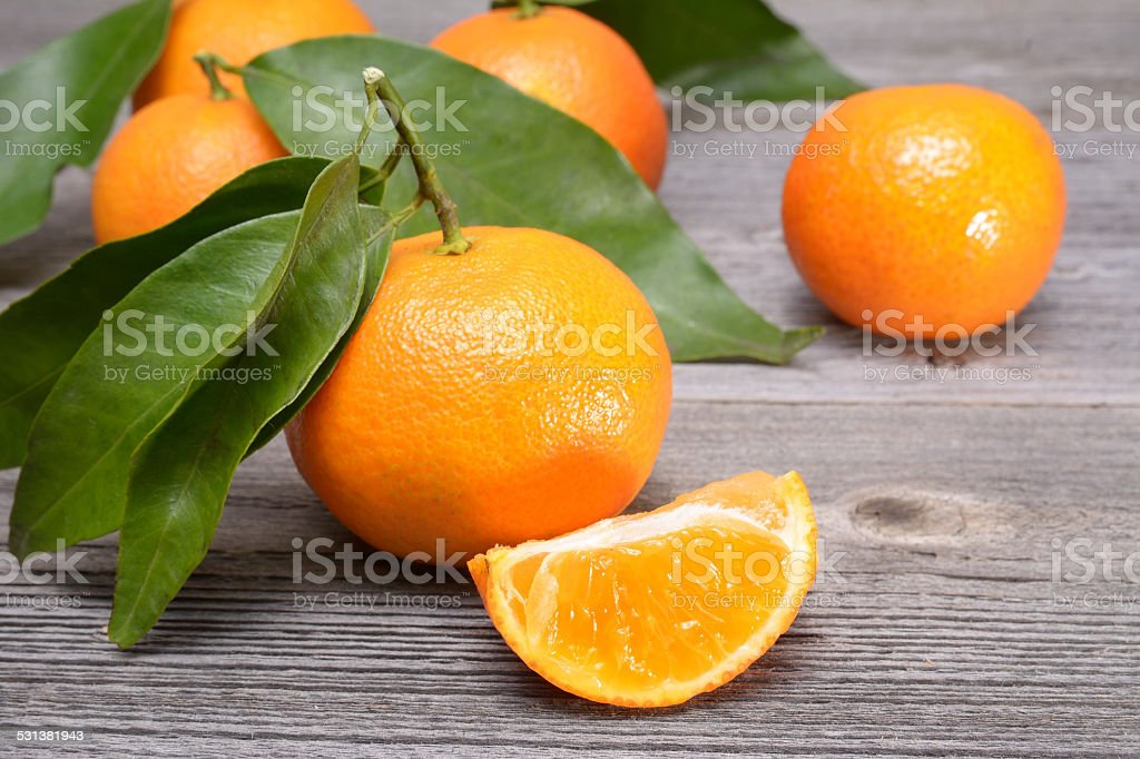 Fresh tangerines isolated on wooden table stock photo