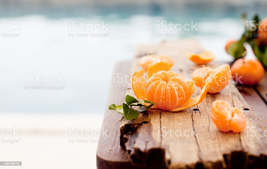 Fresh tangerines on a wooden table blue, sea, water background stock photo