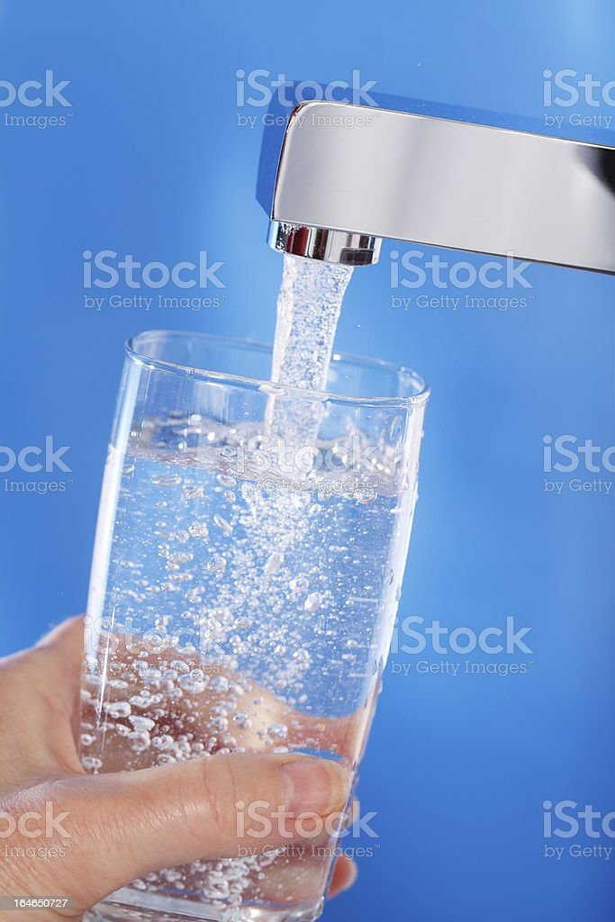 Filling up a glass of water . Blue background.