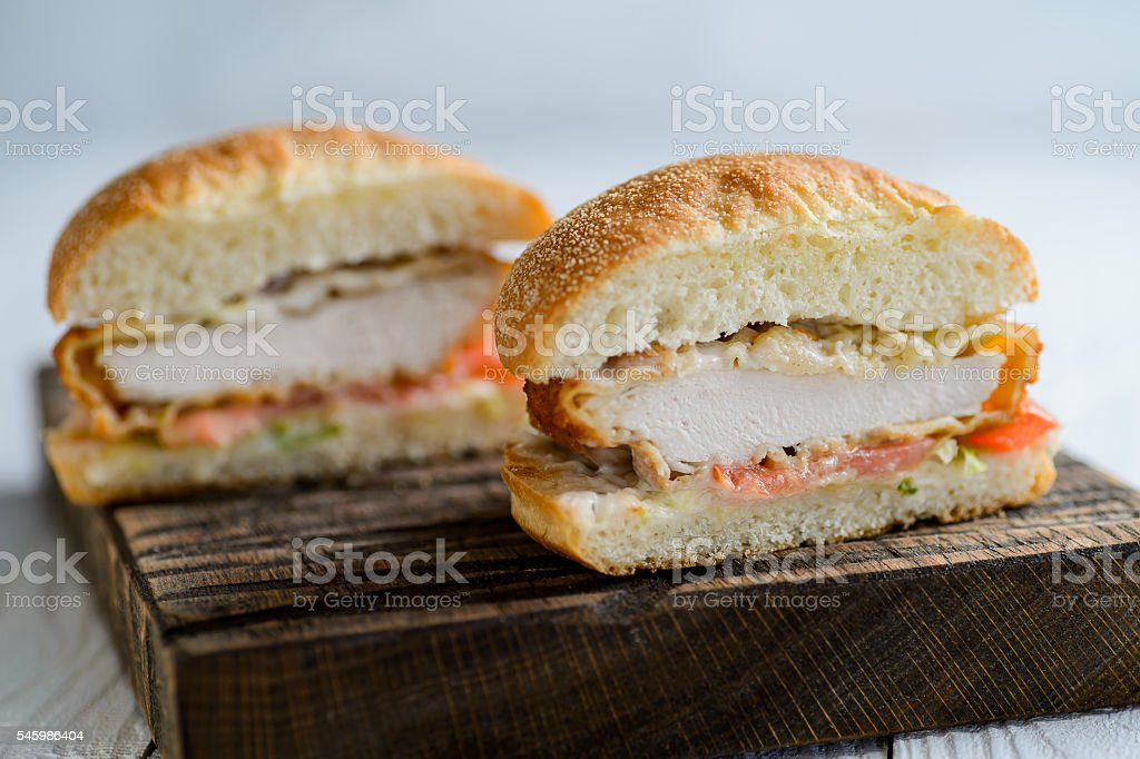 Fresh tasty chicken burger sectional view on wooden table stock photo