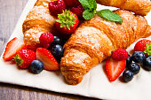 Fresh tasty croissants with berries on wooden background