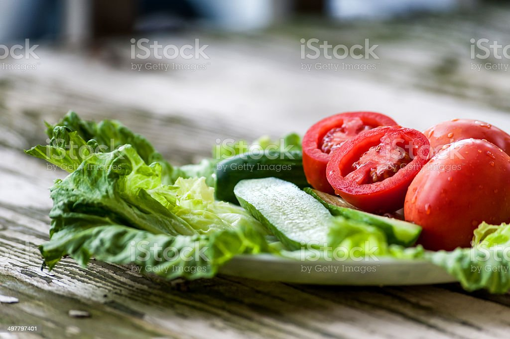 Fresh tomato, cucumber and salad on the plate stock photo