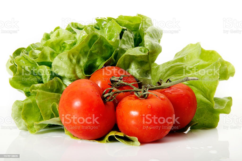 Fresh tomatoes and lettuce on a white background stock photo