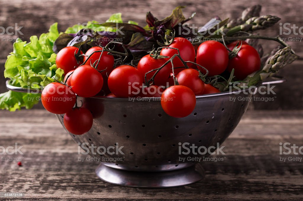 fresh tomatoes and vegetables on wooden background stock photo