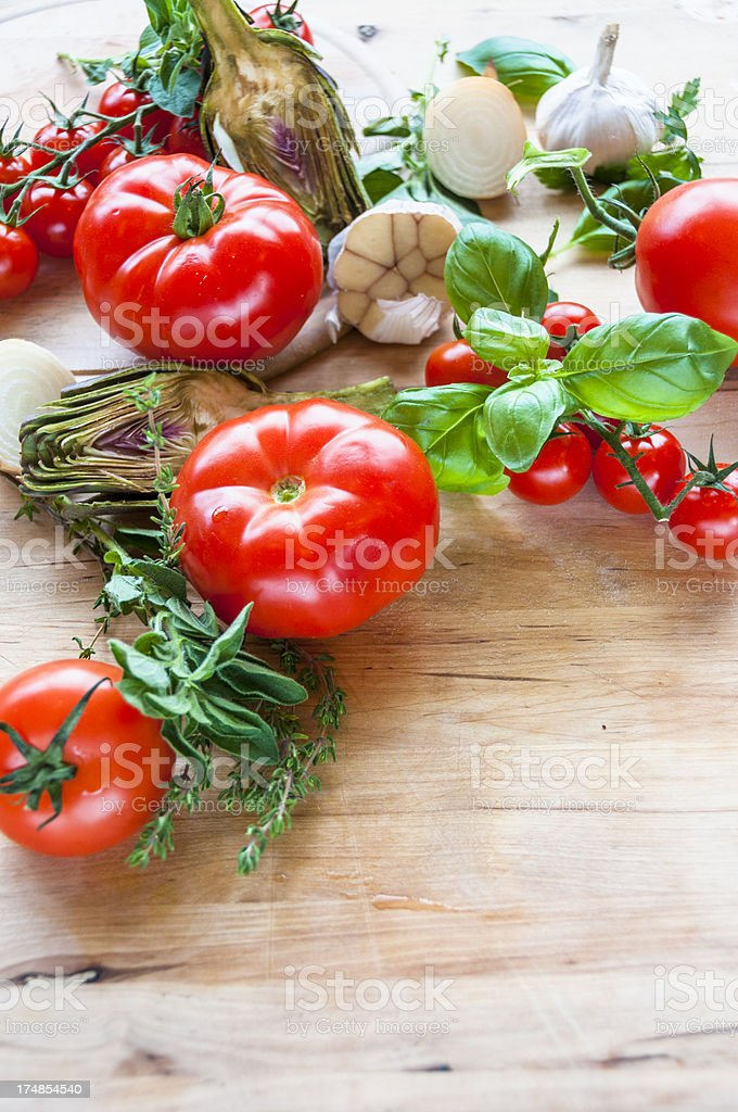Fresh Tomatoes, Artichoke And Garlic On A Wooden Board royalty-free stock photo