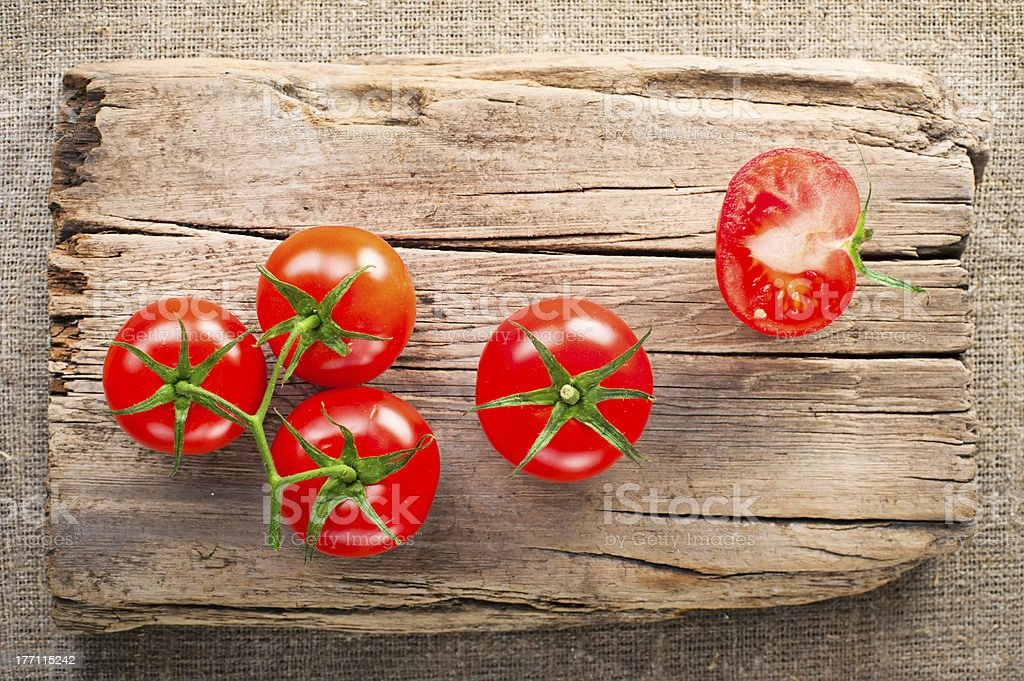 Fresh tomatoes on vintage wooden cutting board royalty-free stock photo