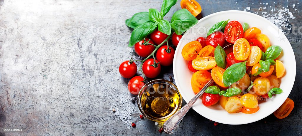 Fresh tomatoes with basil leaves in a bowl stock photo