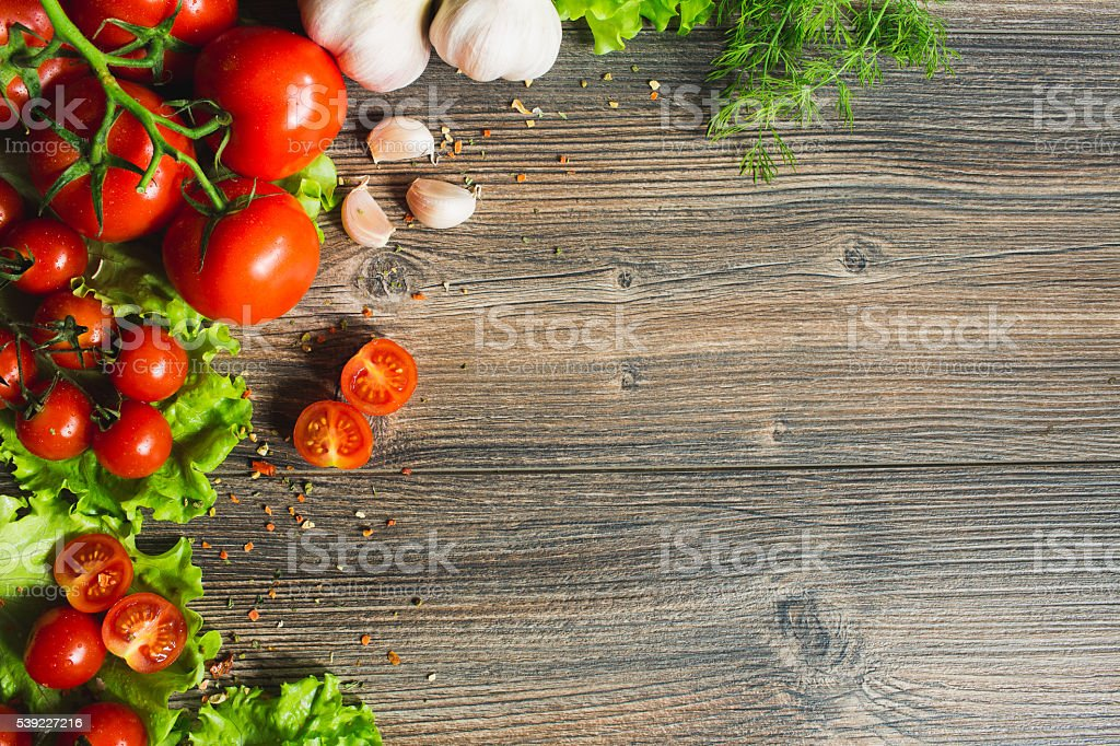 Fresh tomatoes with salad leaves on the table. stock photo