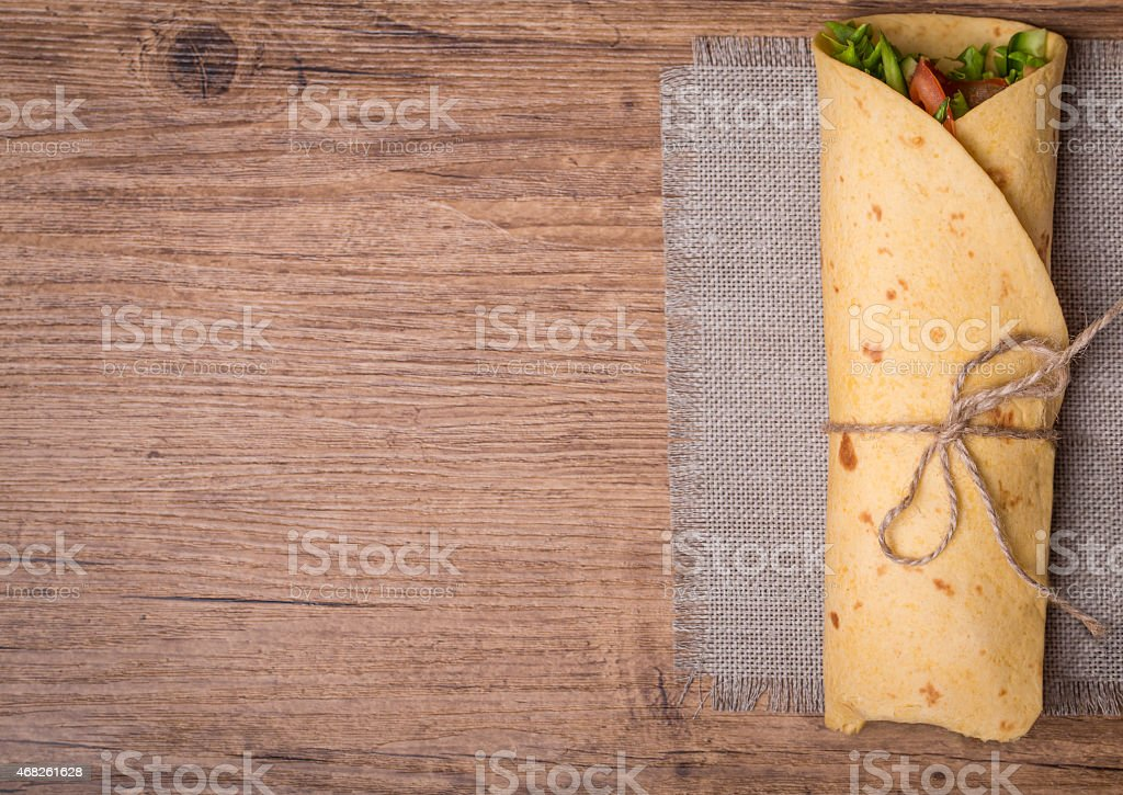 Fresh tortilla wrap tied with rope filled with vegetables stock photo
