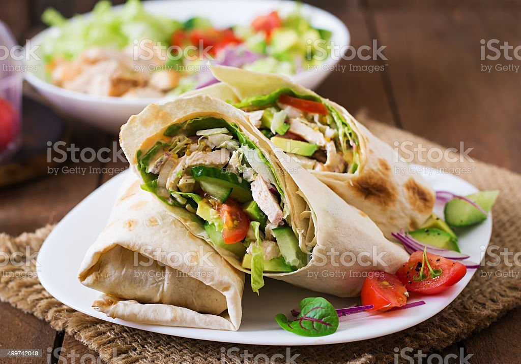 Fresh tortilla wraps with chicken and fresh vegetables on plate stock photo