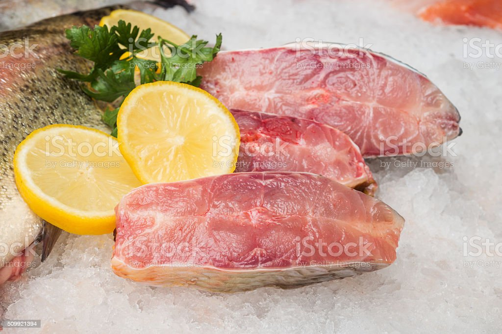 Fresh trout fish and fillet with ice and lemons stock photo