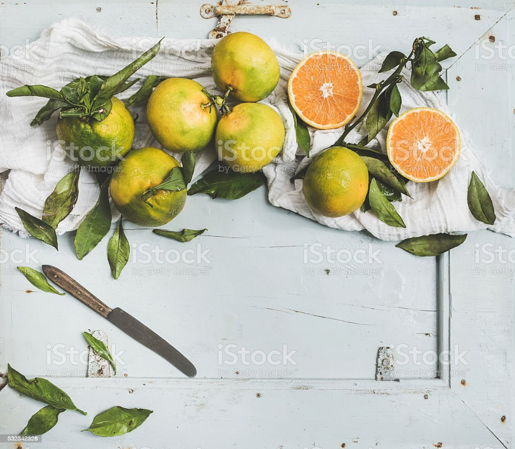 Fresh Turkish tangerines with leaves over blue rustic wooden backdrop stock photo