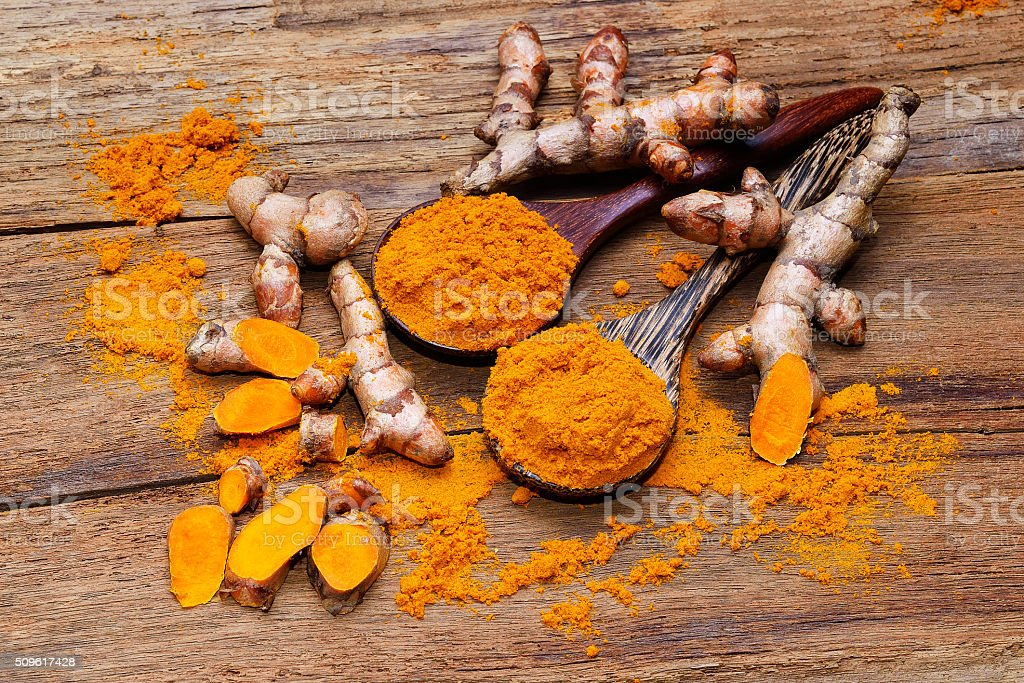fresh turmeric roots on wooden table stock photo