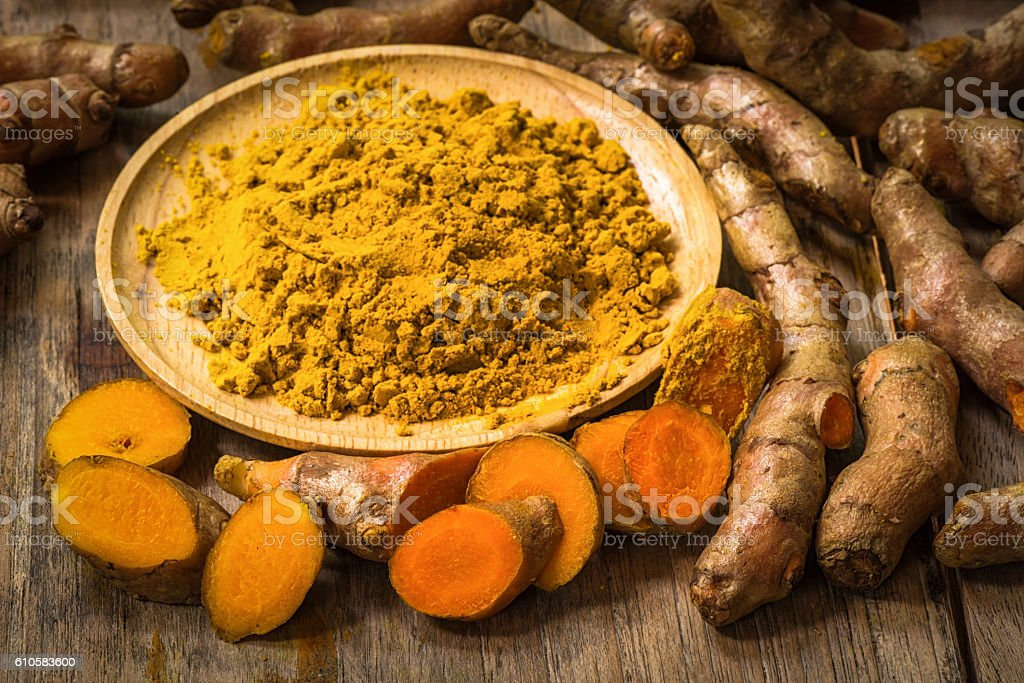 Fresh turmeric roots with turmeric powder stock photo
