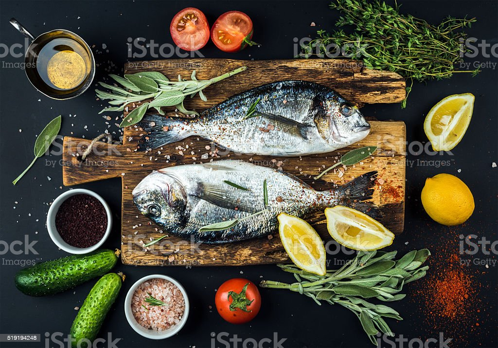 Fresh uncooked dorado or sea bream fish with lemon, herbs stock photo
