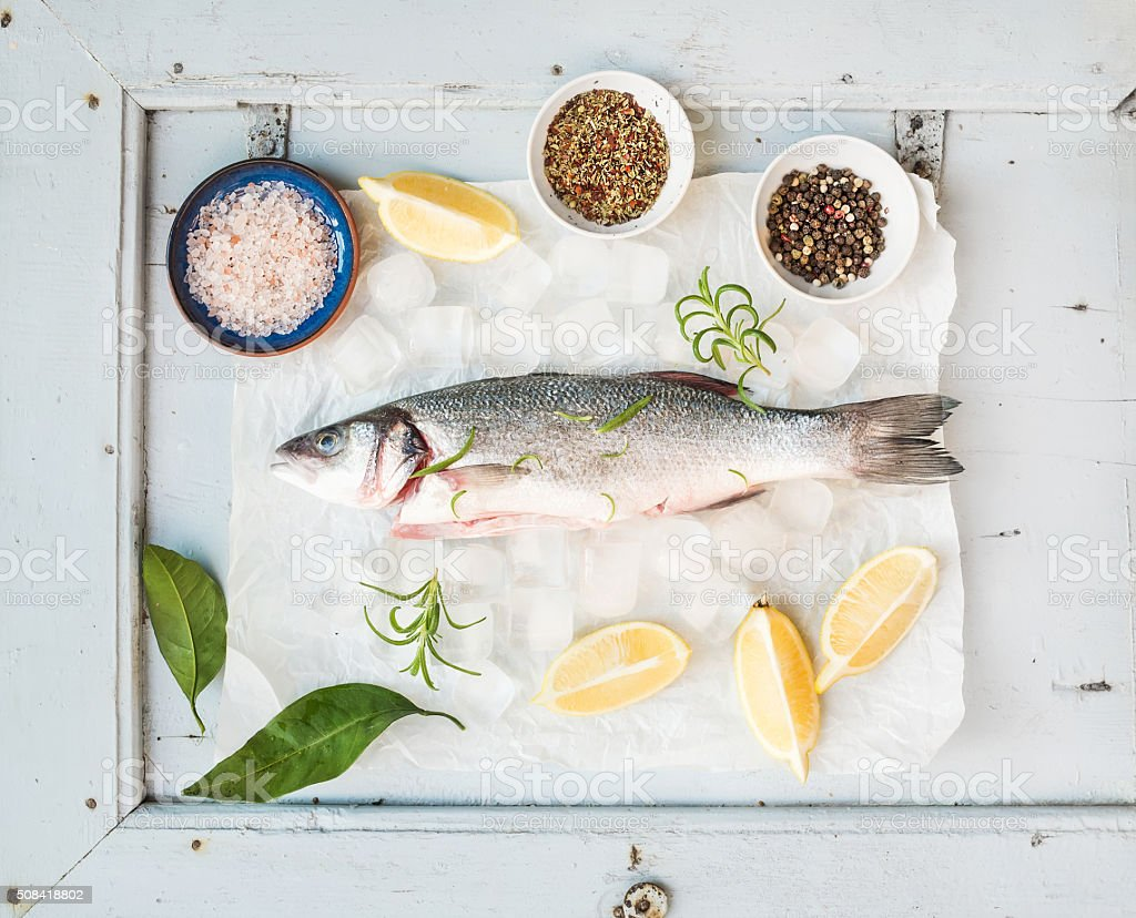 Fresh uncooked seabass fish with lemon, herbs, ice and spices stock photo