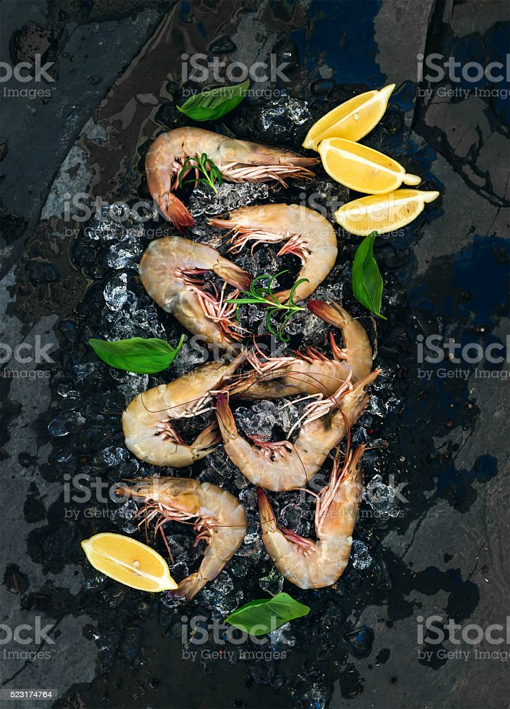 Fresh uncooked shrimps with lemon, herbs and spices on chipped stock photo