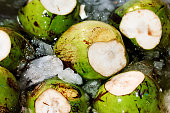 Fresh unpeeled coconuts in ice