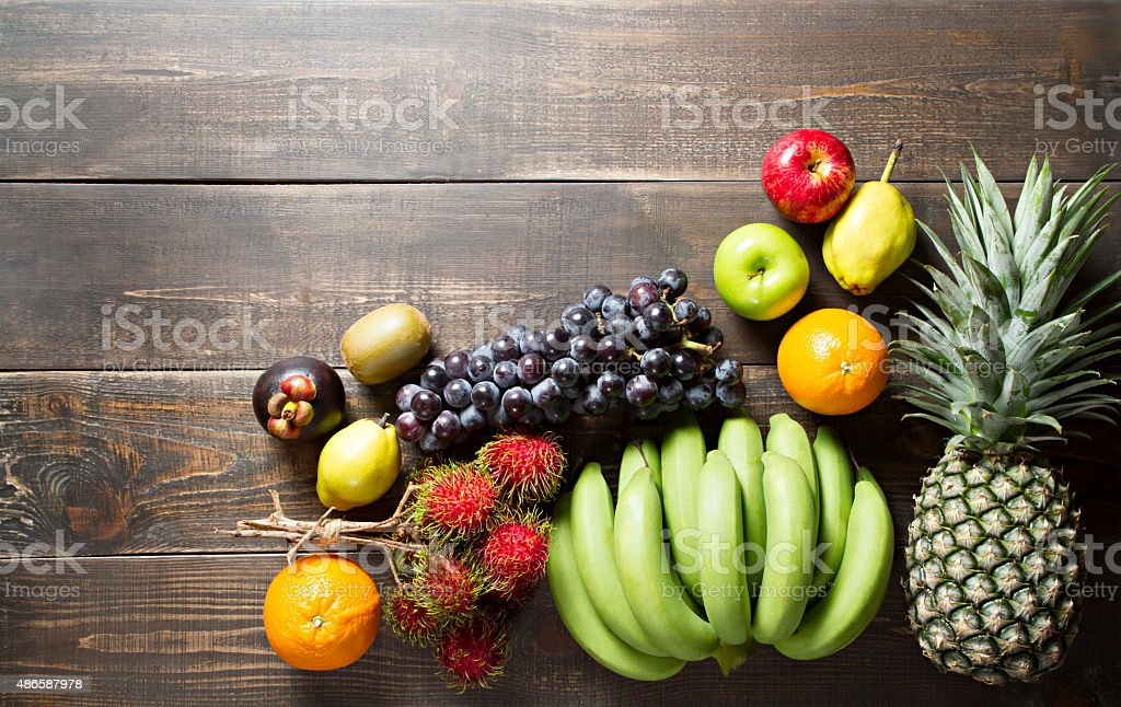 Fresh various fruits on wooden background. stock photo