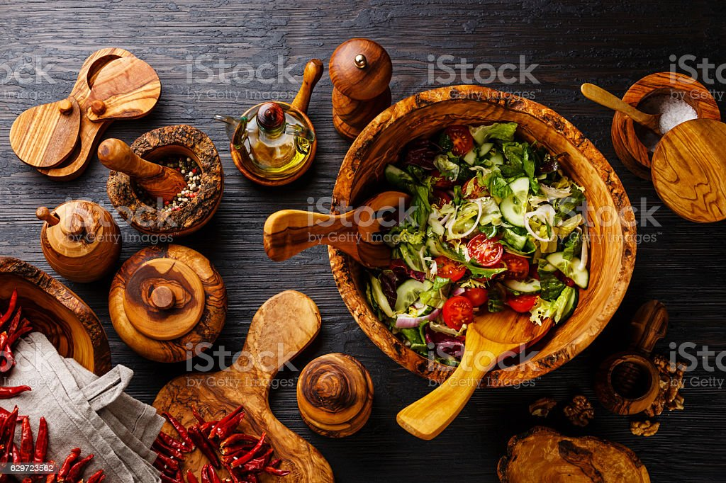 Fresh vegetable salad and wooden tableware stock photo