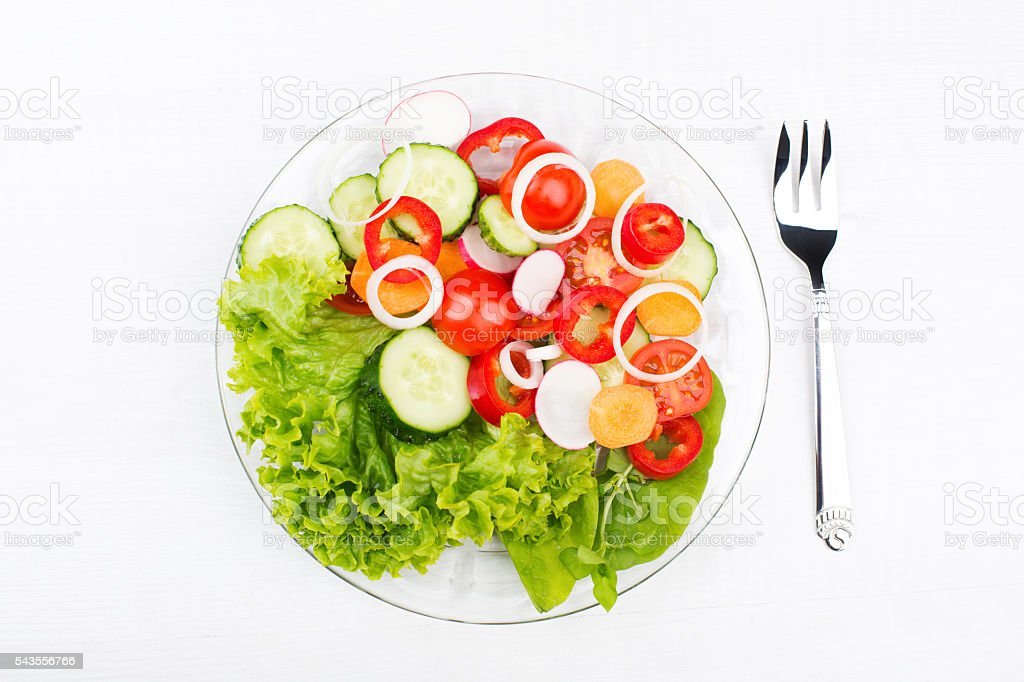 fresh vegetable salad in a glass dish with fork isolated stock photo