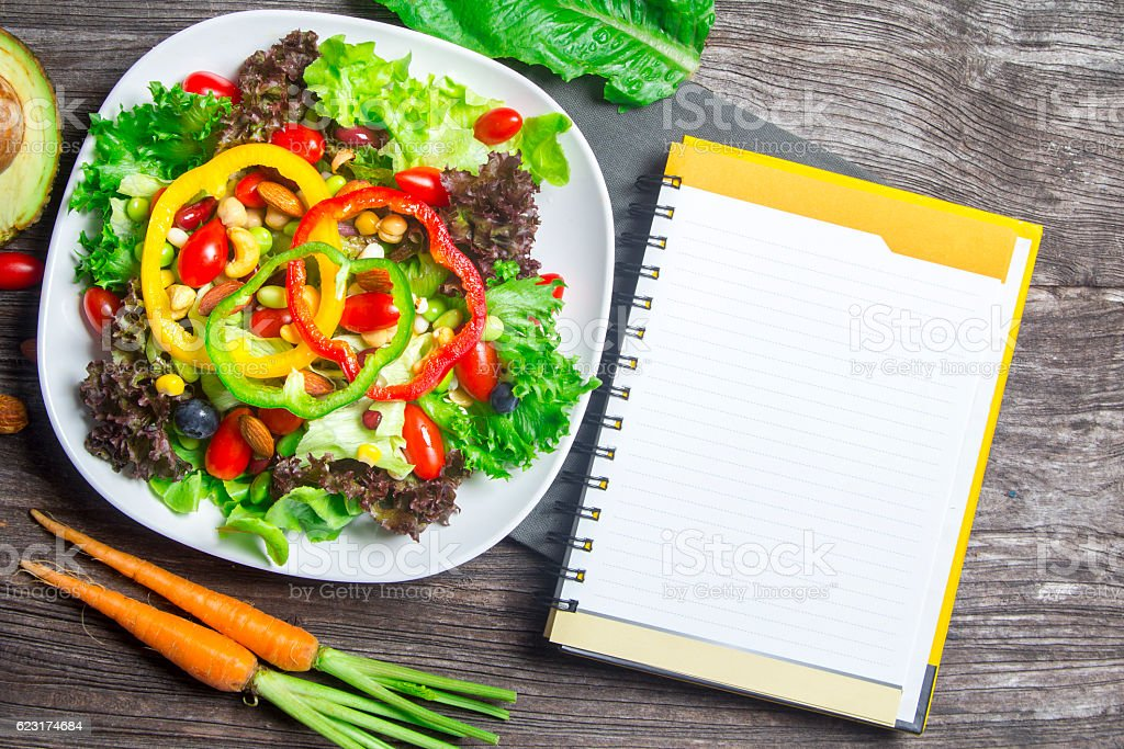 fresh vegetable salad with notebook paper on wood table stock photo