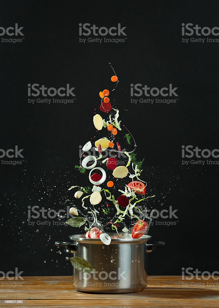 Fresh vegetables falling into a stainless steel casserole stock photo