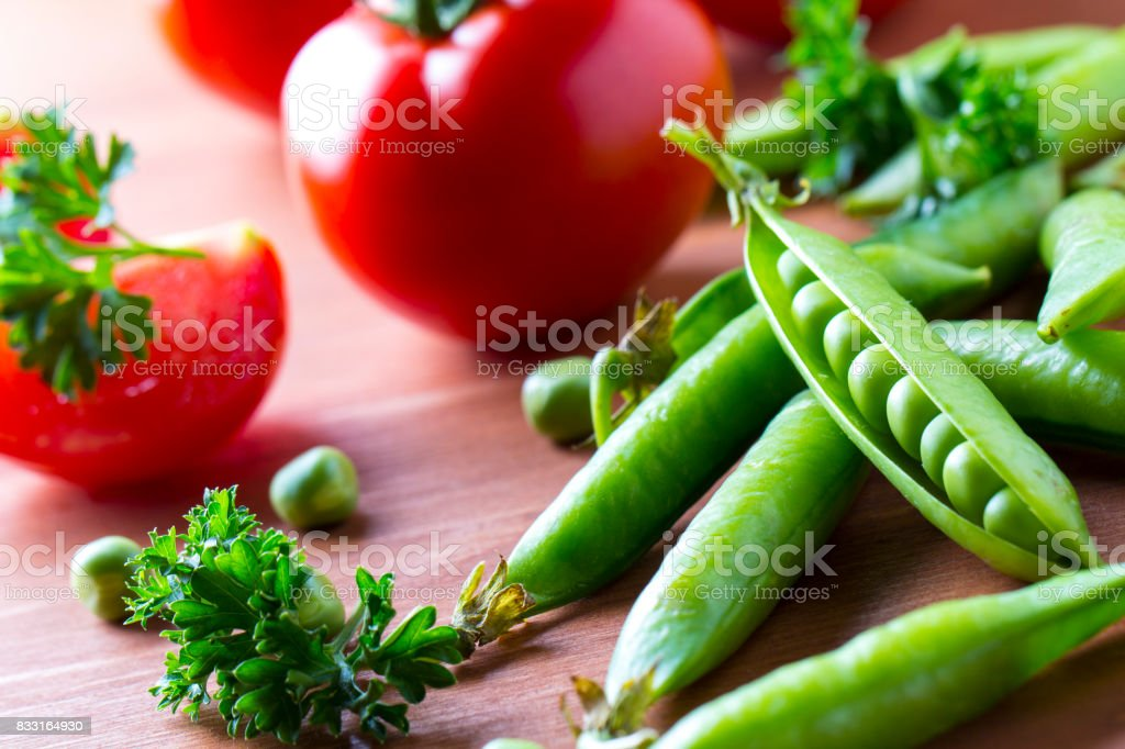 Fresh vegetables Green peas tomatoes dill Wooden stock photo