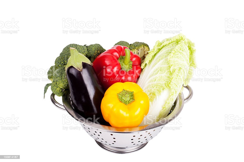 Fresh vegetables in metal colander over white royalty-free stock photo