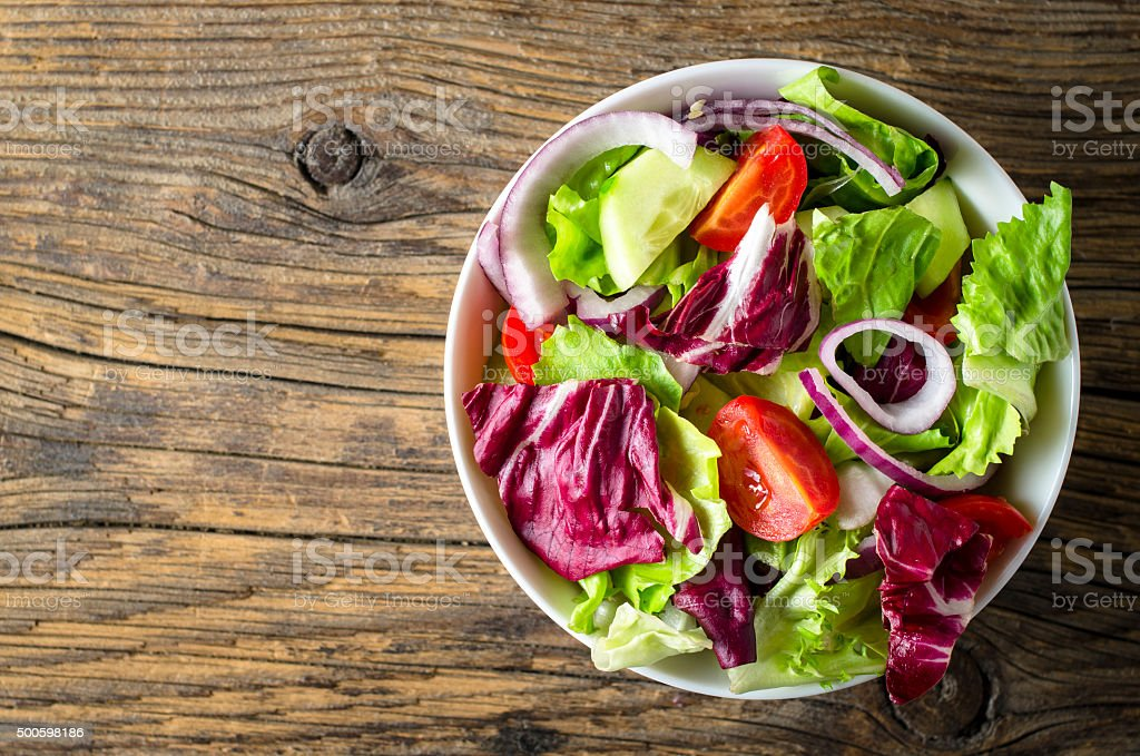 Fresh vegetables salad on wooden table stock photo