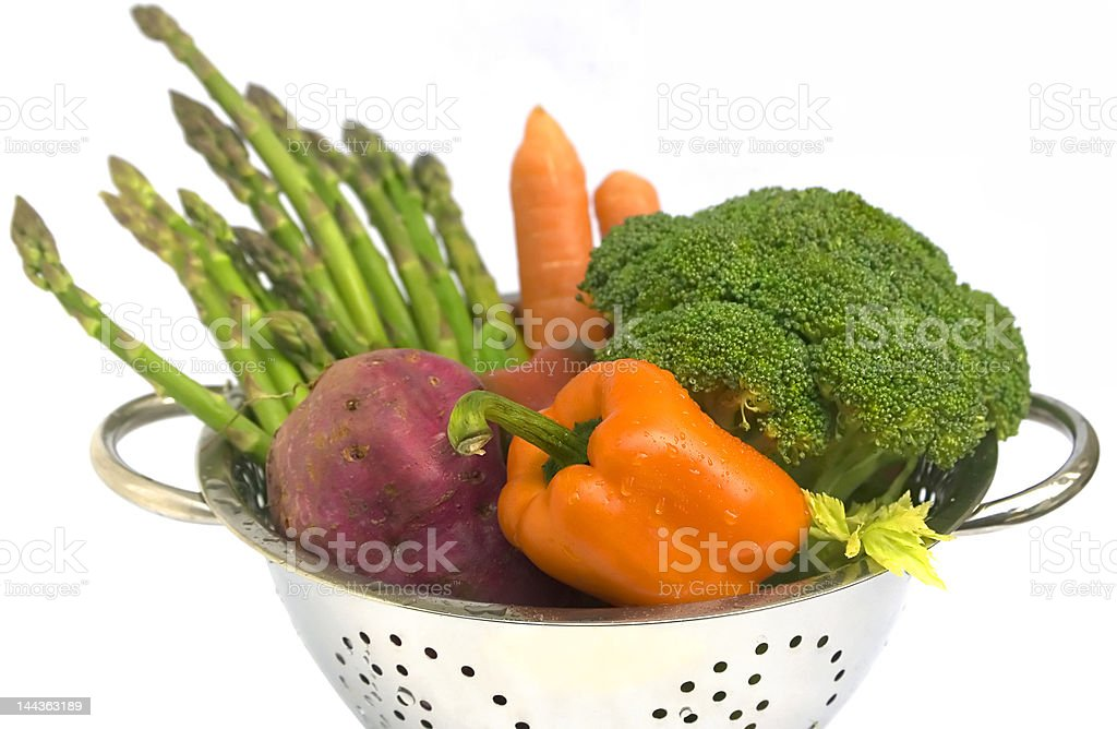 Fresh vegetables with water drops in colander on white isolated stock photo