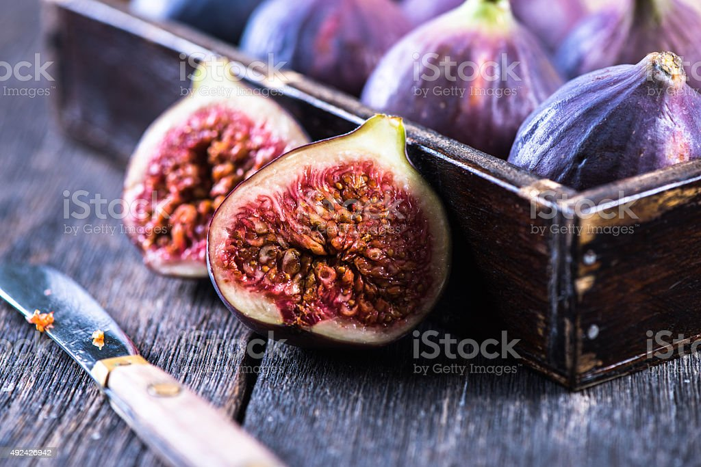Fresh vibrant whole figs and cut in half stock photo