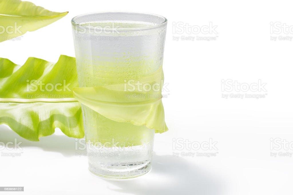 fresh water in glass with green leaf on white background stock photo